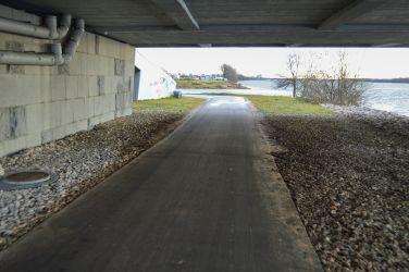 Turpinājumā ceļš ved zem Salu tilta, kur izveidots savienojums ar tālāk esošo ietvi.
