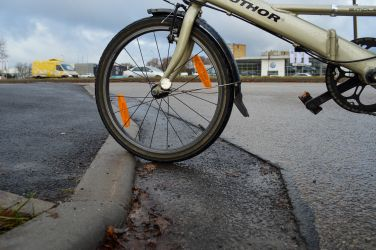 [...] realitātē apmales joprojām nav nolīdzinātas, pie tam izveidota bedre, jo arī asfalts vairs nav vienādos līmeņos.