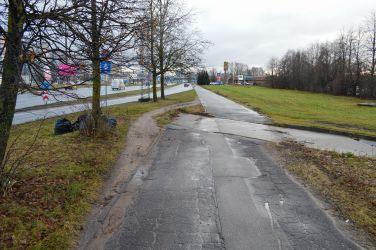 Turpinājumā pilnīgi bezjēdzīga iebrauktuve, kas pat nav savienota ar brauktuvi. Kā redzams pēc izbraukātā zāliena, velosipēdisti apmales apbrauc pa zāli.